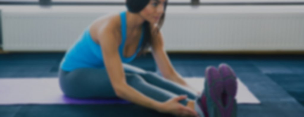 Young fit woman doing yoga exercises on yoga mat at gym