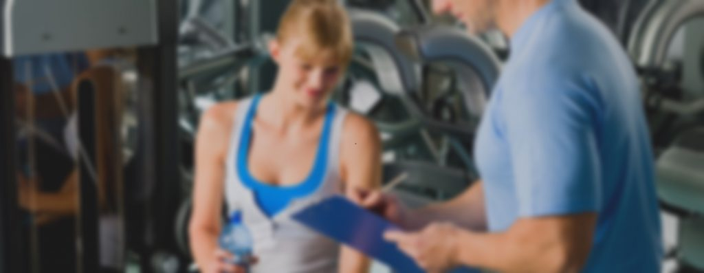 Young woman completing personal fitness plan with trainer healthy club